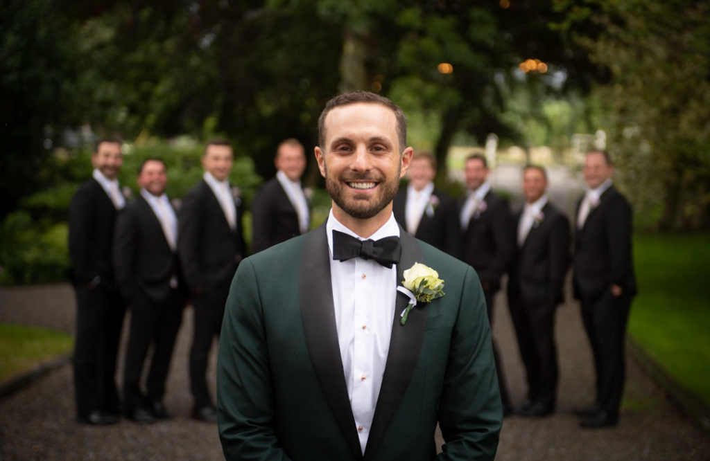 Groom in green suit in foreground and his groomsmen in the background all looking at camera