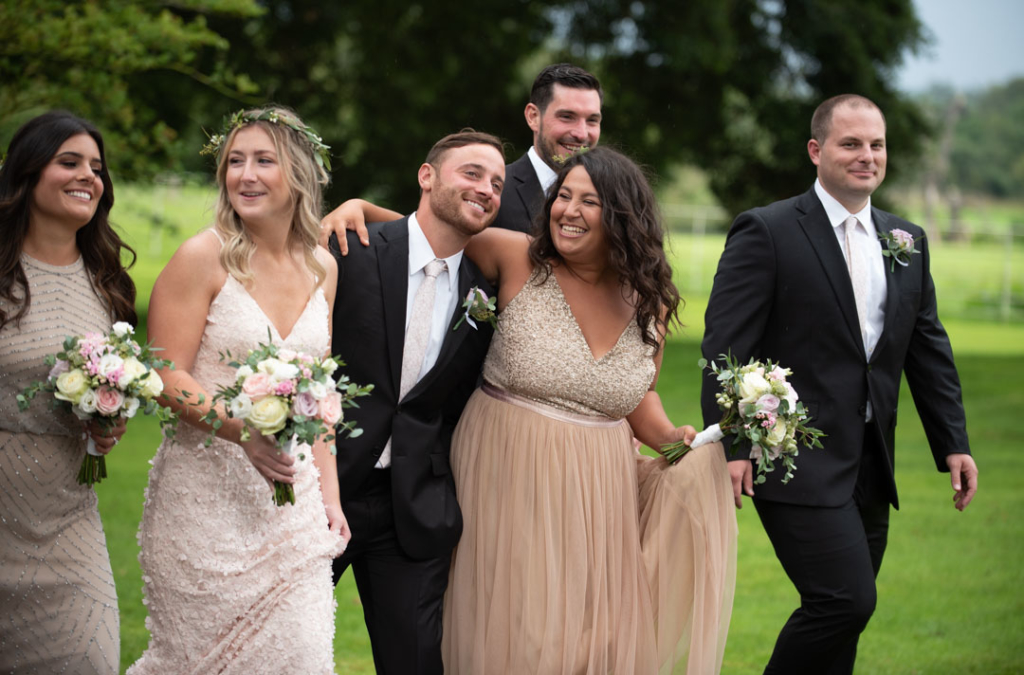 Bridal party walking and laughing together in the Ballymagarvey village grounds