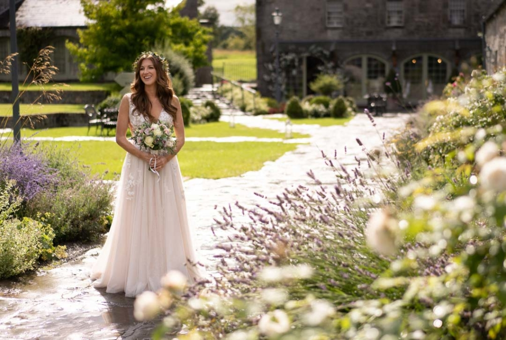 Bride standing in the courtyard at Ballymagarvey village surrounded by summer flowers