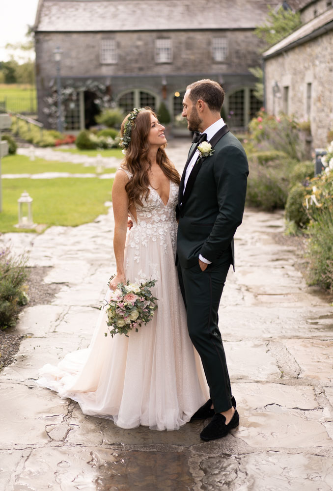 Bride and Groom standing looking at each other in the courtyard at Ballymagarvey Village