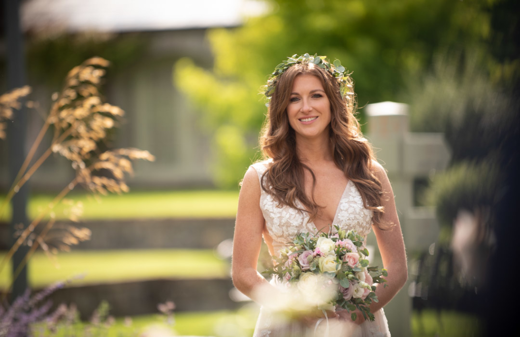 Bride holding her flowers with flower crown on her head surrounded by garden flowers