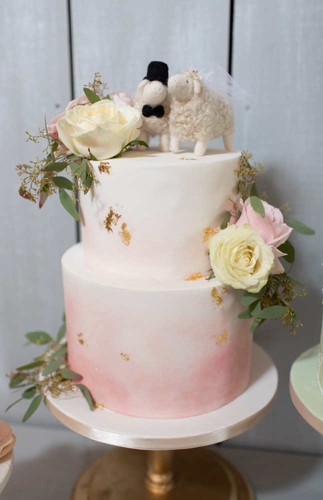 White and blush two tier wedding cake with flowers on it