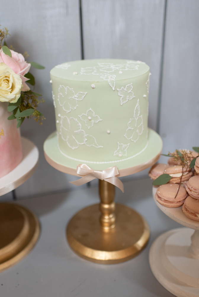 Green one tier wedding cake with white pearls and decoration sitting  on a gold cake stand