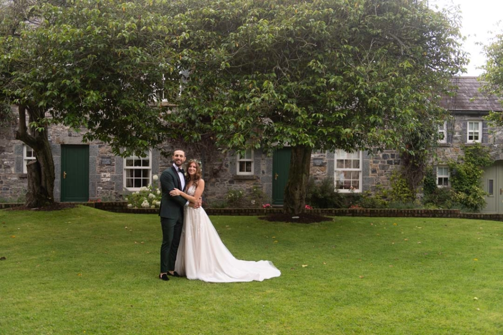 Bride and Groom standing on grass arm in arm smiling at camera in the courtyard of Ballymagarvey