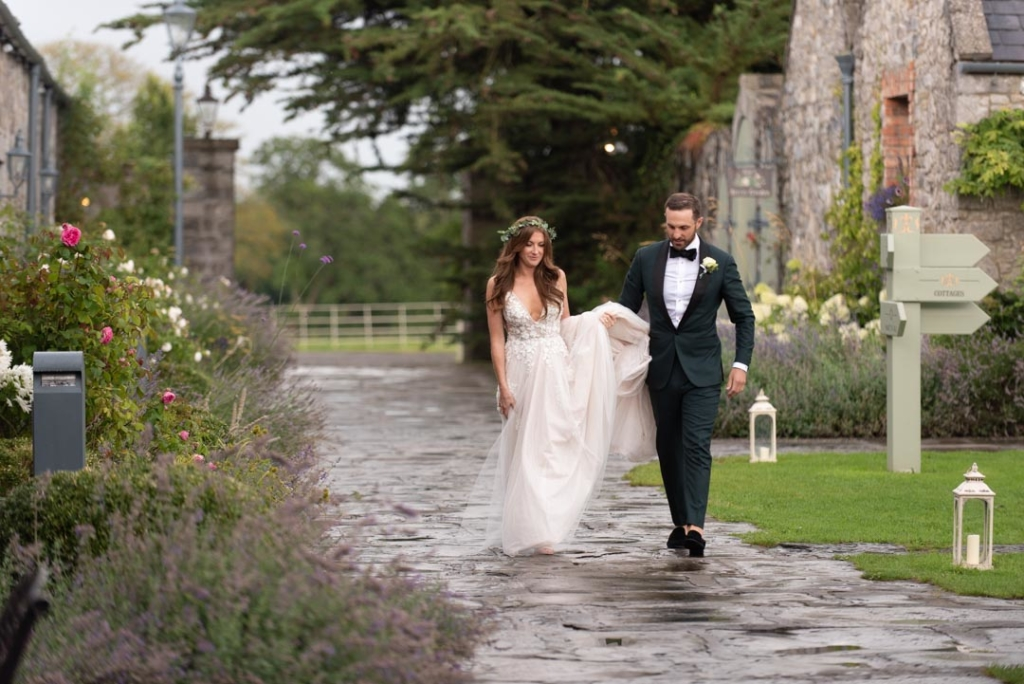 Groom holding up Brides dress as they walk through Ballymagarvey