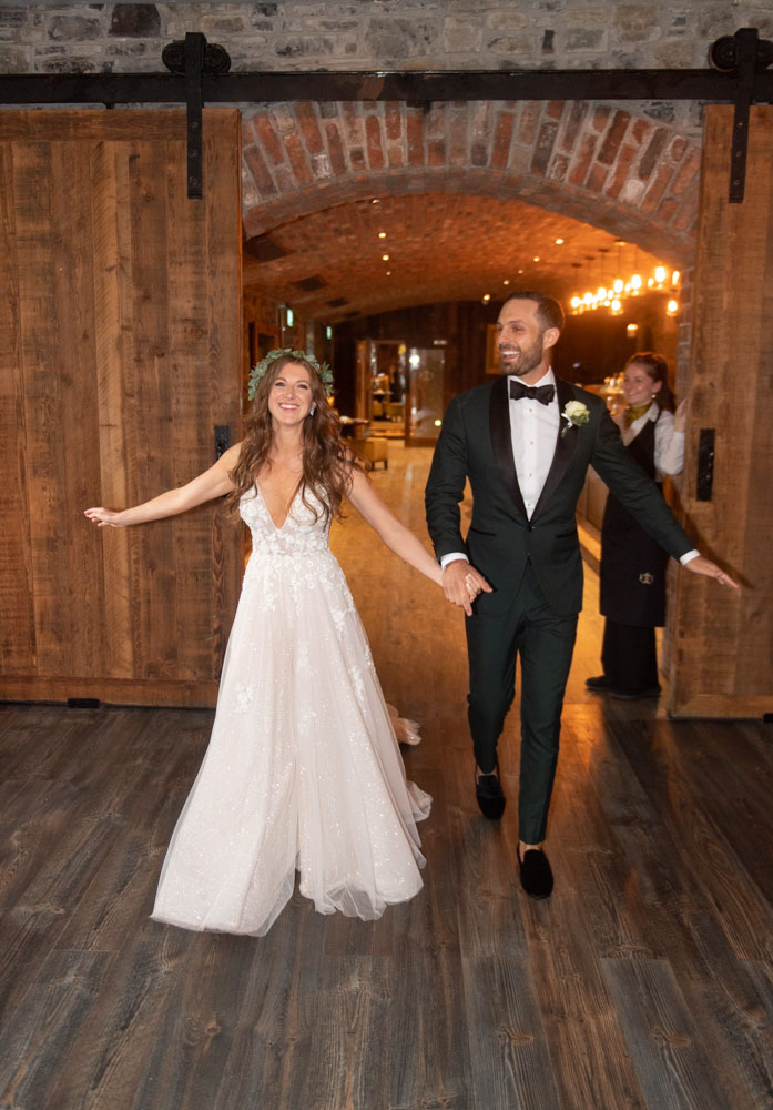 Bride and Groom smiling swinging their arms as they walk into their dinner reception