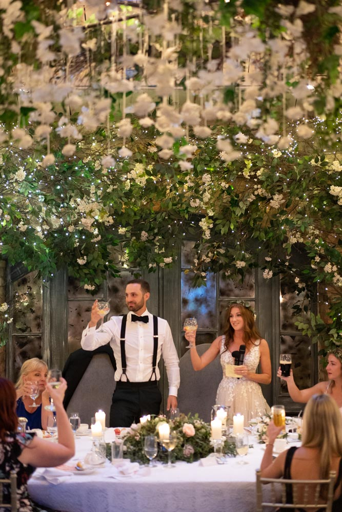 Bride and Groom standing while holding their wine glasses up at the top table at Ballymagarvey