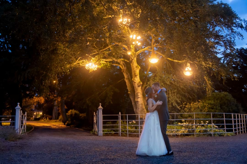 Bride and groom outside at night time kissing under the tree full of lit chandeliers at Ballymagarvey