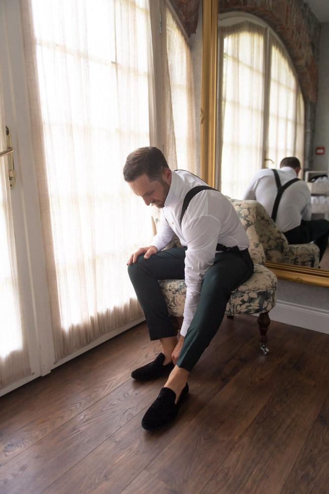 Groom seated putting on his black velvet slip on shoes