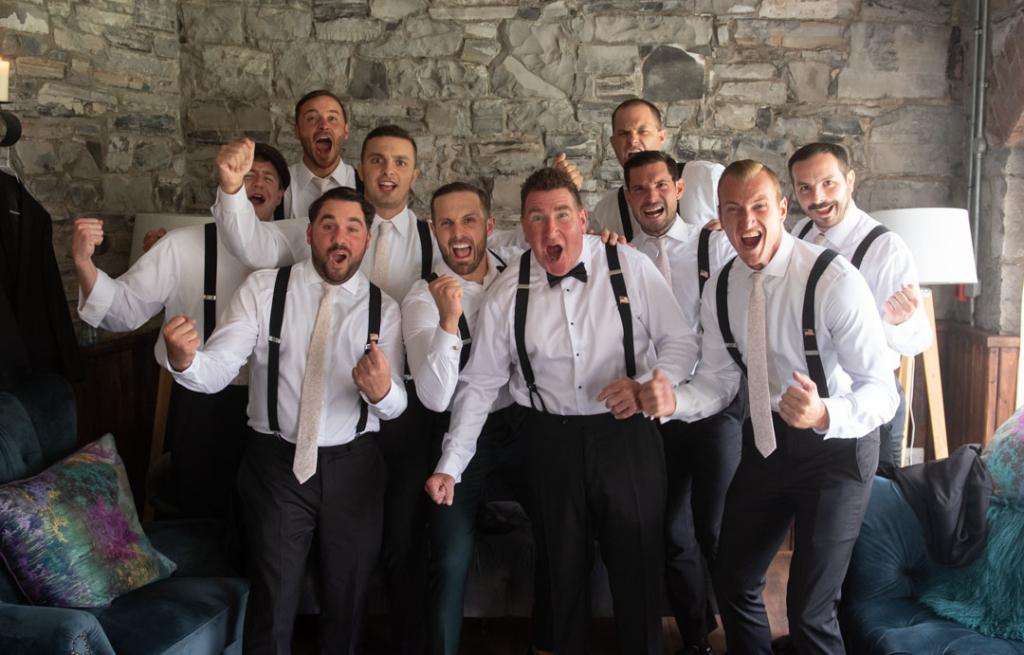 Groom and his groomsmen cheering looking at camera