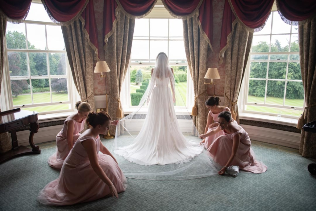 Bride standing in the window of the K Club while her bridesmaids fix her veil