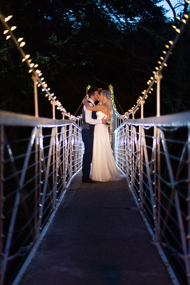 Bride and groom kissing on the K Club bridge at night with the bridge lit up with fairy lights