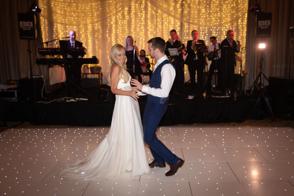 Bride and groom dancing their first dance on the white led dance floor