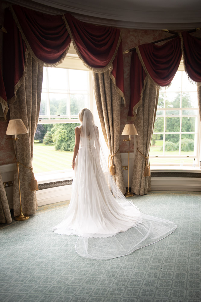 Bride standing in wedding dress looking out the window at the K Club