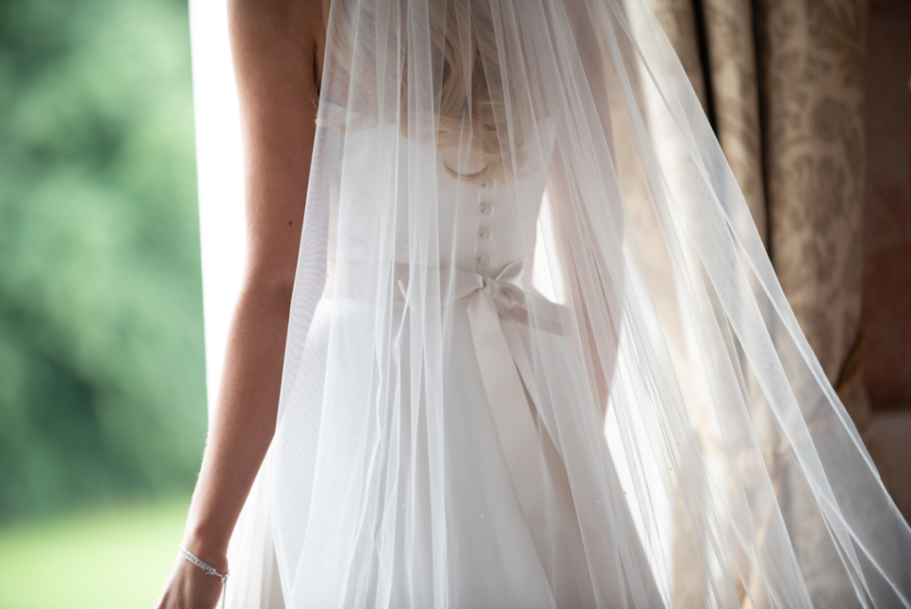 Blush bow and white buttons under veil on the back of the brides wedding dress
