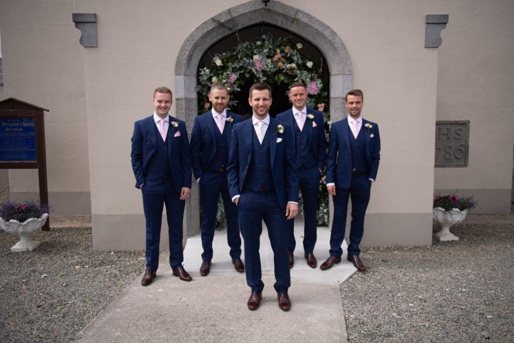 Groom and his groomsmen standing in front of the door of the Church
