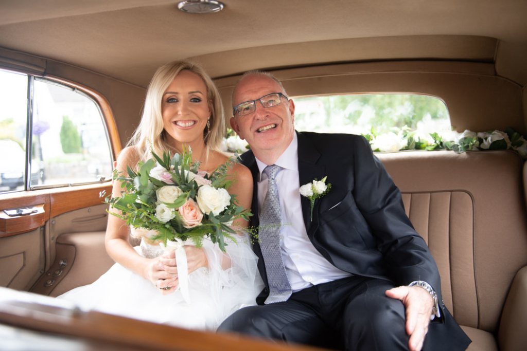 Bride and her dad in the back seat of the wedding car outside the Church