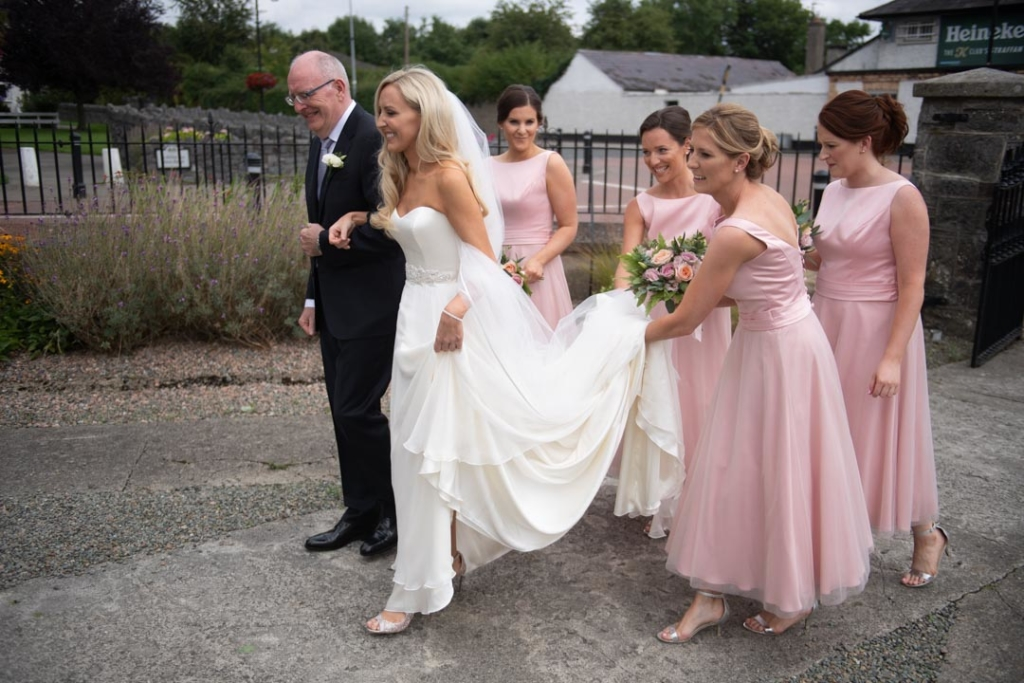 Bridesmaids holding brides dress as she walks to the church door with her dad