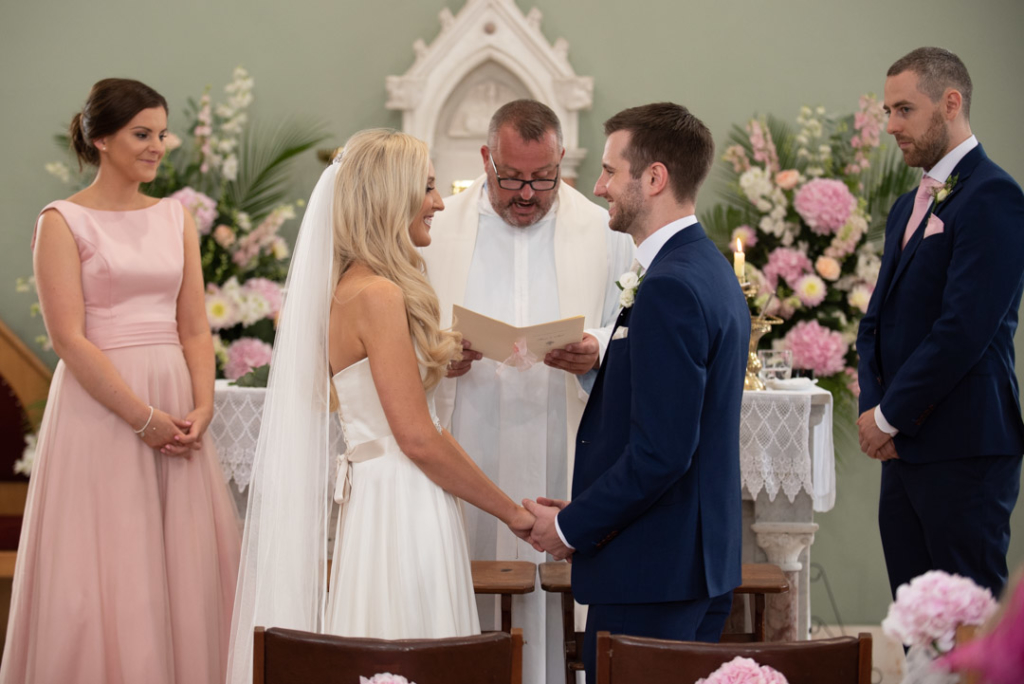 Bride and groom holding hands facing each other at the top of the aisle saying vows