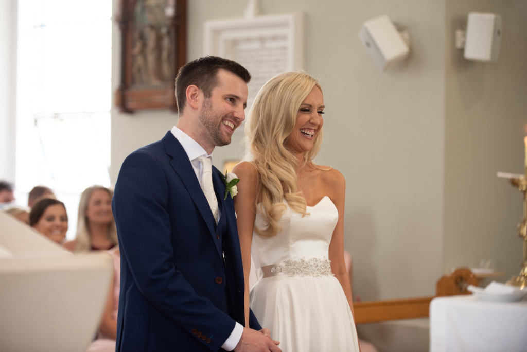 Bride and groom laughing in the Church