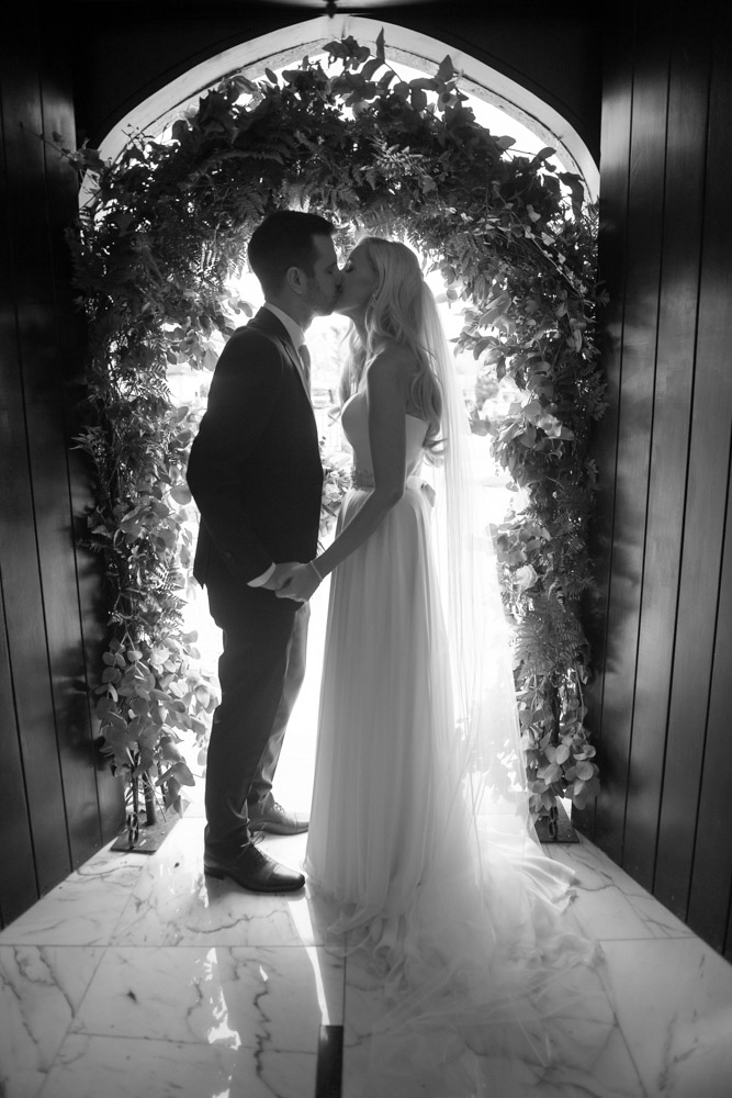 Black and white photo of bride and groom kissing in the Church door