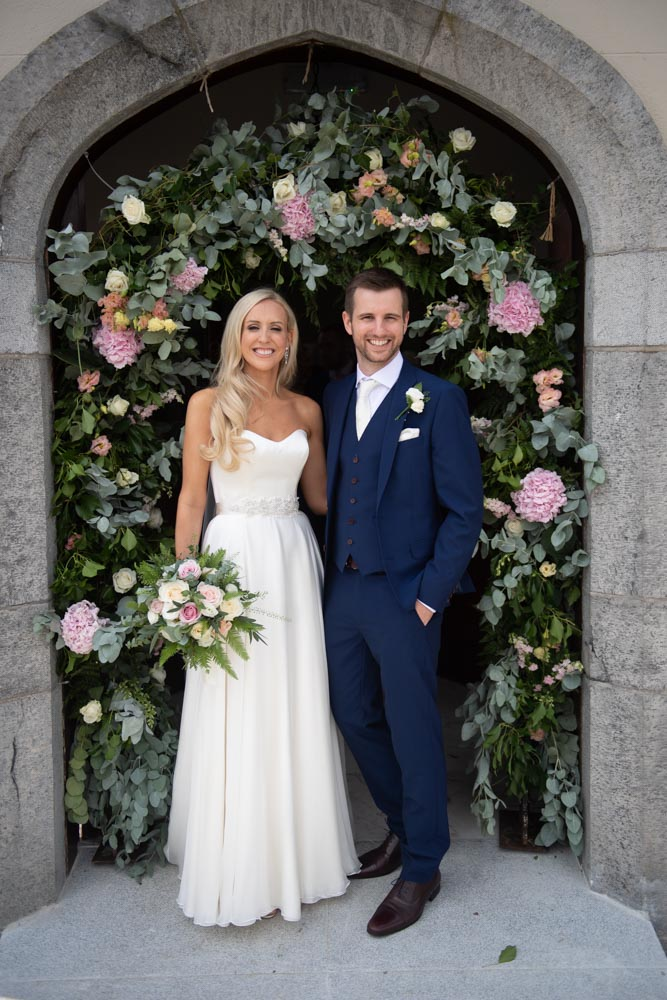 Bride and groom standing in the Church door surrounded by a flower arch