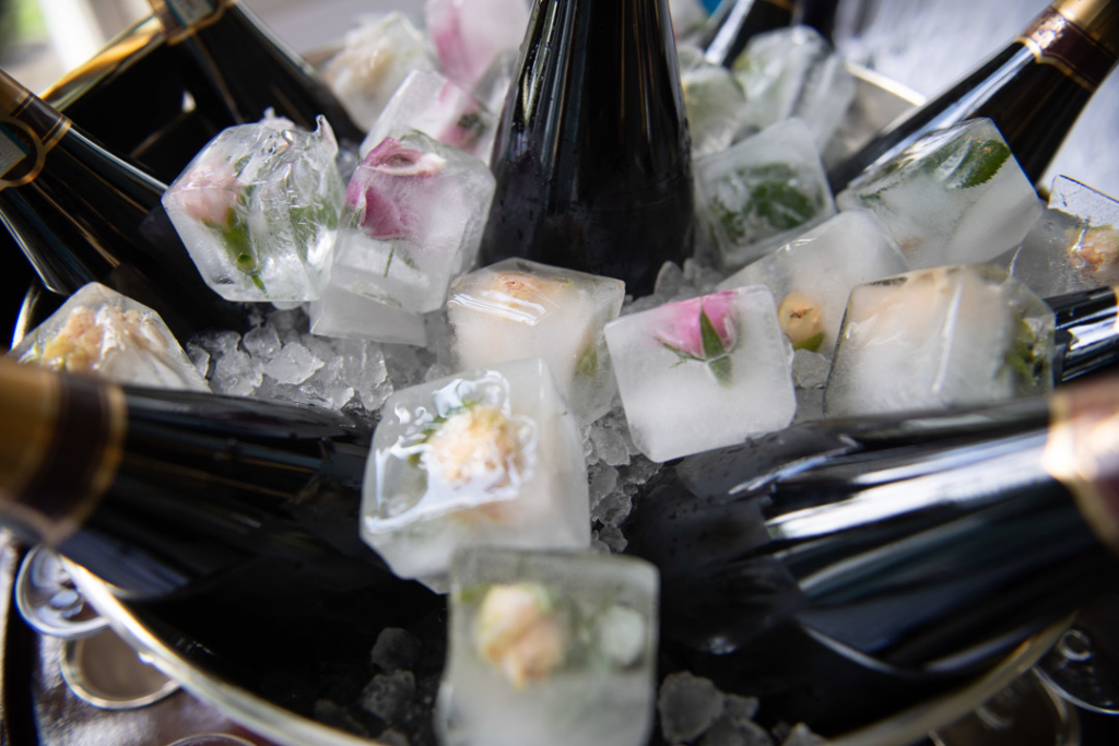 Champagne bottles in ice bucket with flowers frozen in ice cubes