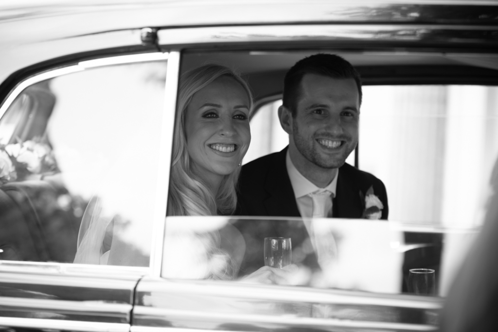 Bride and groom in the back of the wedding car at the K Club