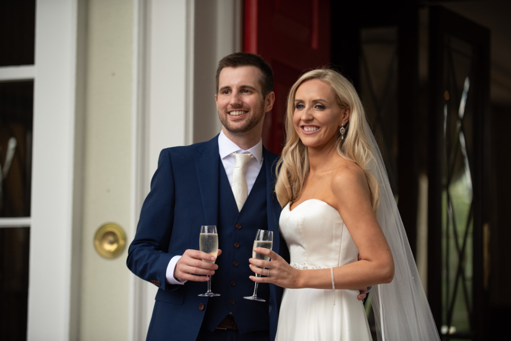 Bride and groom smiling and holding champagne glasses at the front door of the K Club