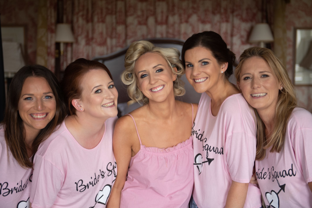 Bride and her bridesmaids wearing pink pyjamas on the morning of wedding