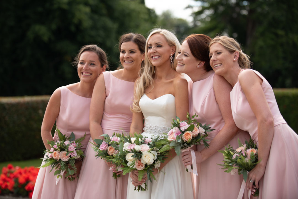 Bride in white and bridesmaids in pink dresses smiling
