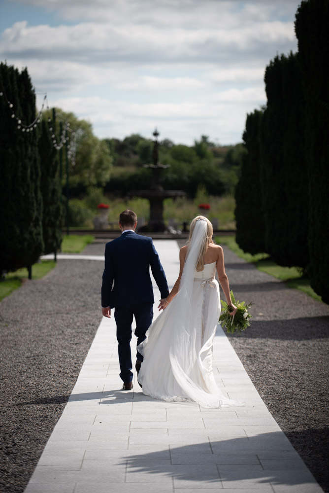 Bride and groom holding hands while walking on the grounds of the K Club