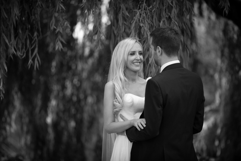 Black and white of Bride and groom smiling at each other on the grounds of the k club