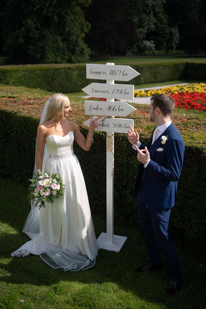Bride and groom pointing towards the sign post that has different countries written on it