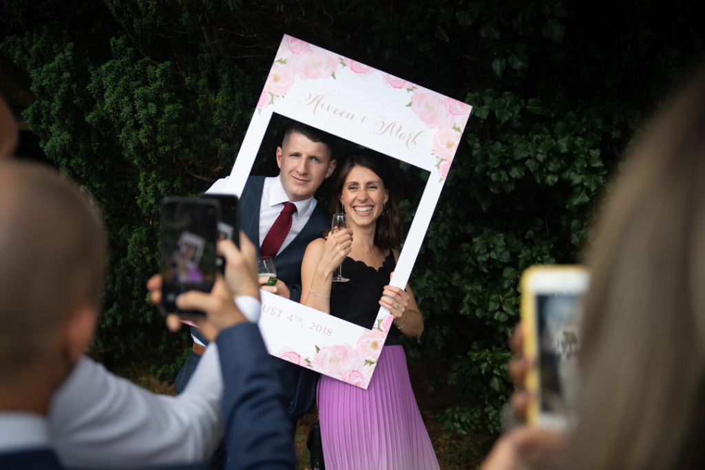 Guests posing for a photo in a big cut out frame