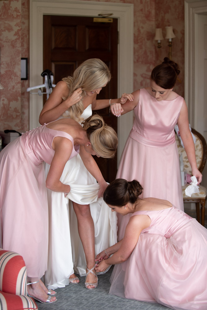 Bridesmaids helping the bride to put on her shoes