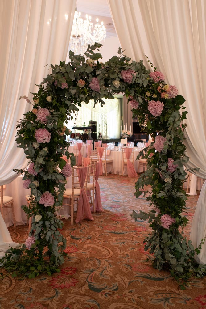 Green flower arch with pink flowers at the entrance into the reception room at the K Club wedding