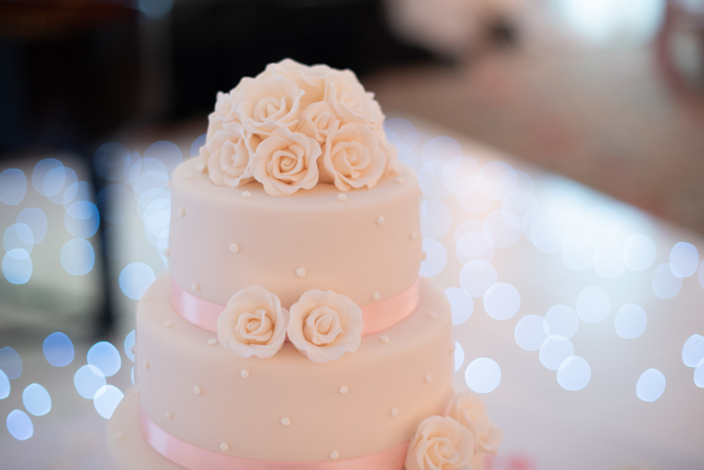 White wedding cake with white flowers made out of icing