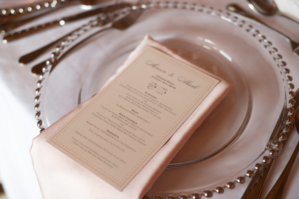 Charger plate with pink napkin and wedding dinner menu on top