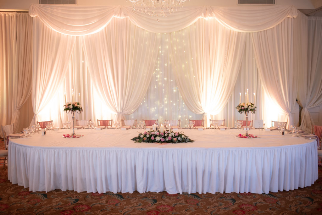 Top table with white drape and fairy lights behind it at the K Club