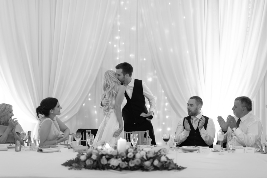 Bride and groom standing and kissing at the top table after giving his speech