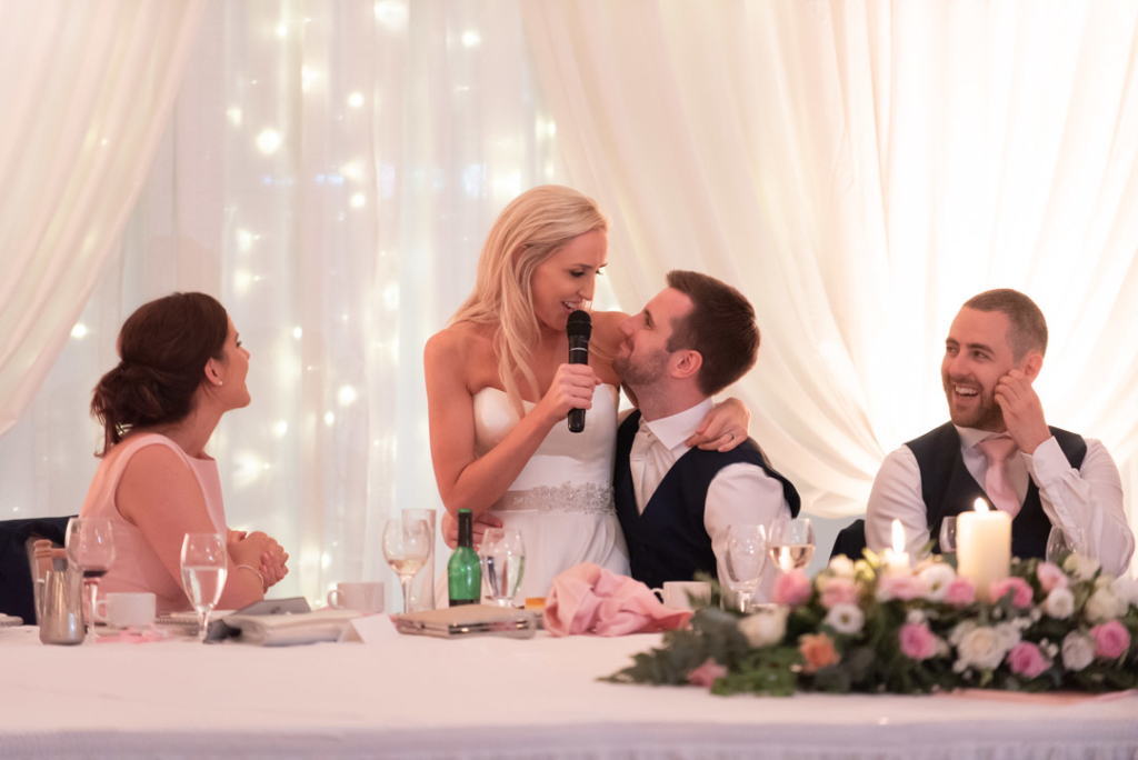 Bride sitting on grooms knee while giving her speech