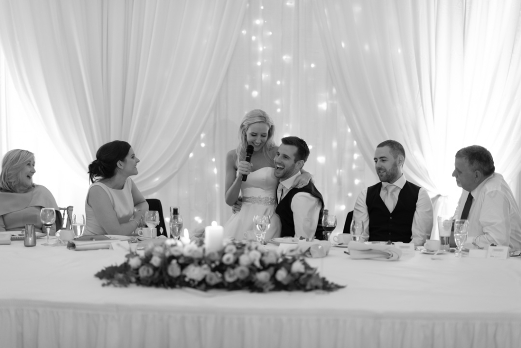Groom laughing while bride is sitting on his knee while giving her speech
