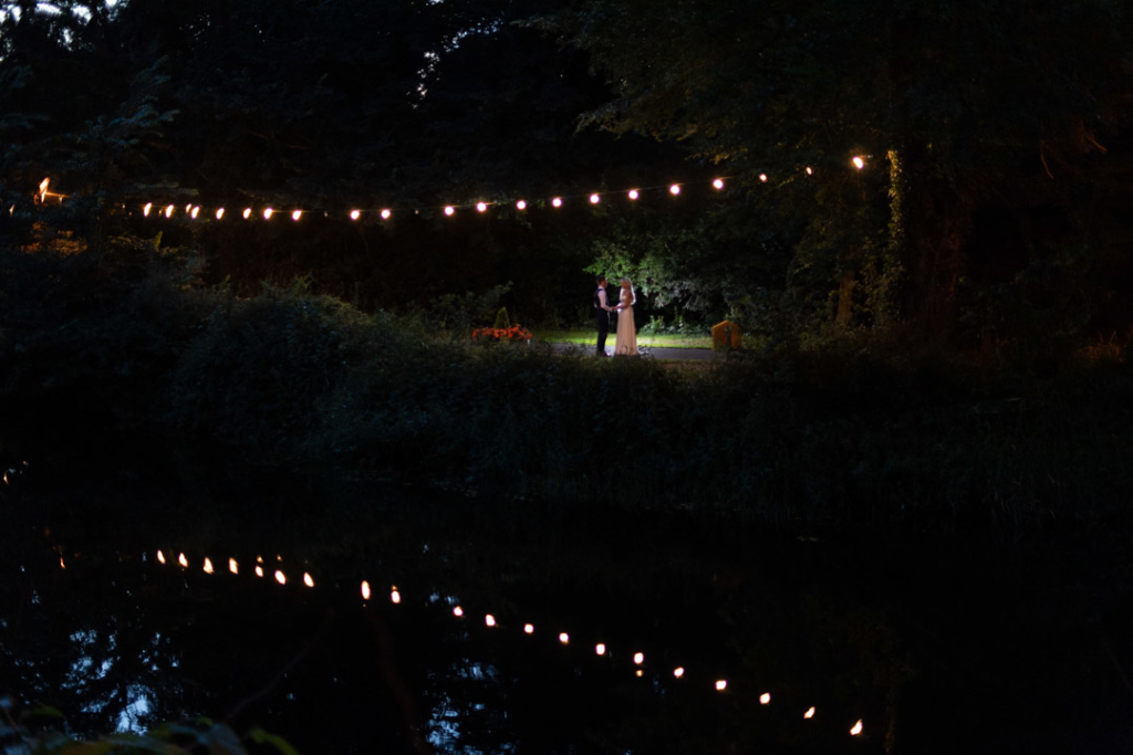 Bride and groom outside in the dark standing under rope lights at the K Club
