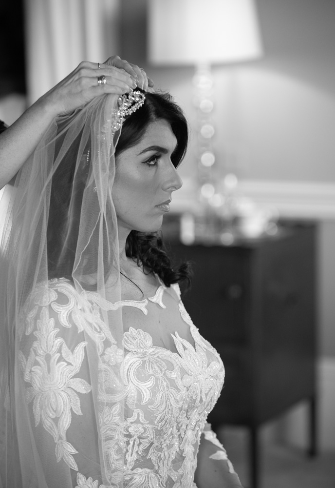 Bride getting her veil put on by hairstylist