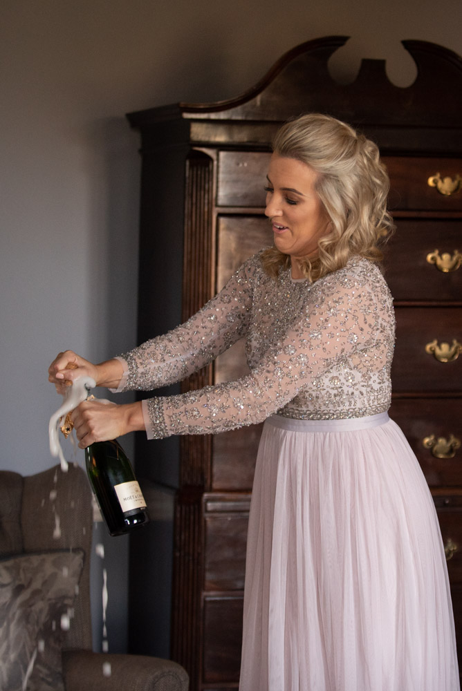 Bridesmaid opening a bottle of Moet champagne