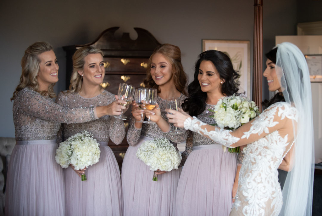 Bride and bridesmaids clinking champagne glasses on the morning of the wedding