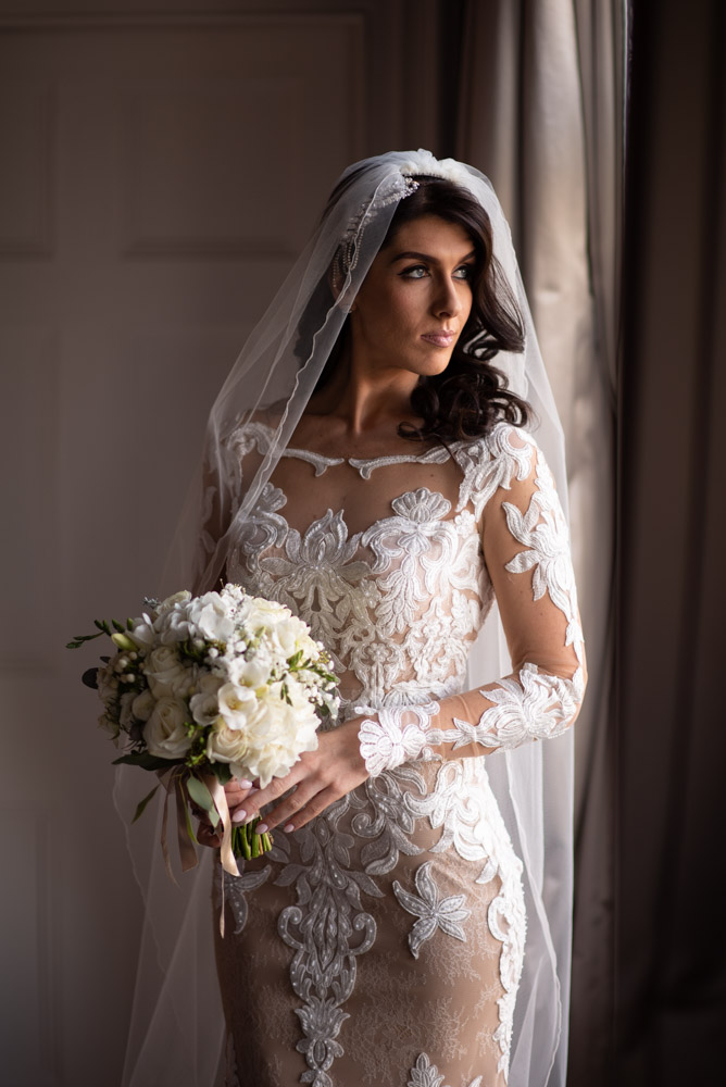 Bride in her wedding dress holding her flower bouquet looking out the bridal suite window