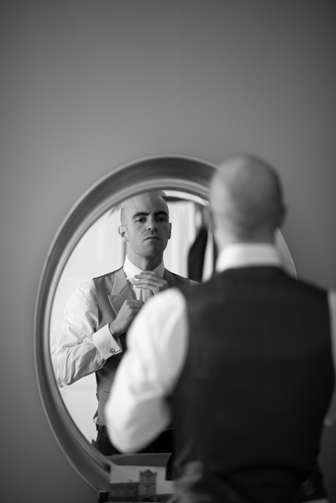 Black and white of Groom tying up his tie in the mirror