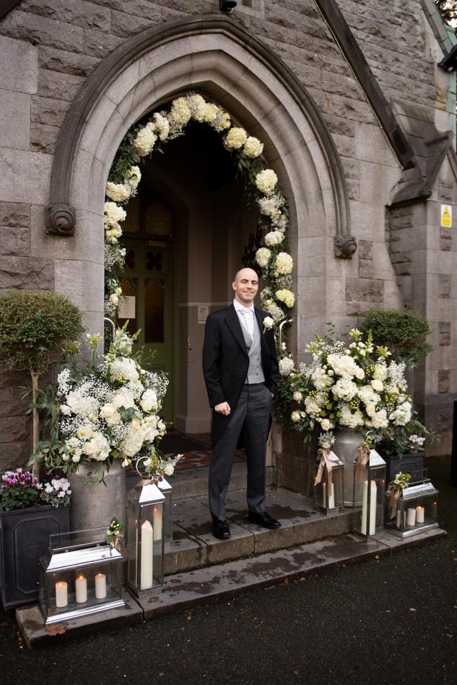 Groom standing in front of the Church door surrounded by a flower arch and candles